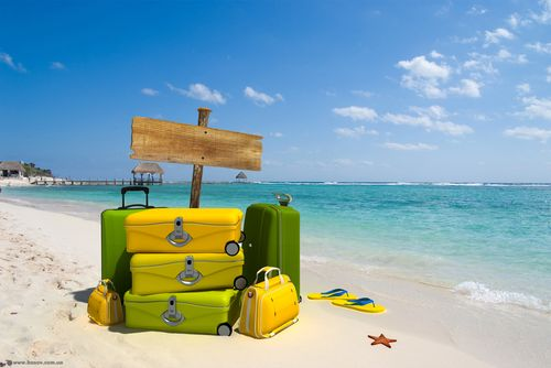 Pile of yellow luggage on a resort beach with a blank wooden sign post